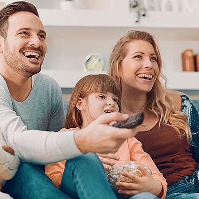 La famille regarde sur la Smart TV en souriant